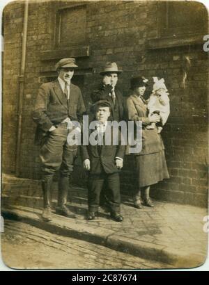 Grupo de personas, posiblemente miembros de la familia, incluyendo un hombre de crecimiento restringido (enanismo), 1920. Fecha: 1920