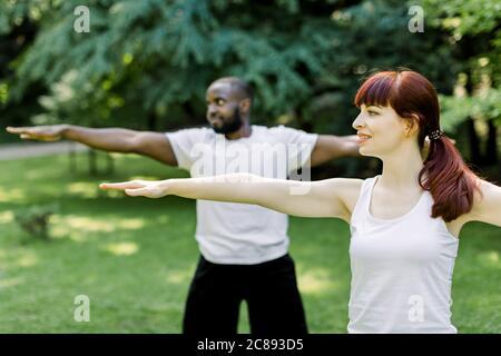 Concepto de un estilo de vida familiar saludable y yoga en el parque. Jóvenes parejas multiétnicas ejercitando al aire libre con los brazos estirados, mirando hacia adelante. Céntrese en