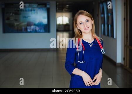 Estudiante de medicina sonriendo en la cámara de la universidad en un traje azul quirúrgico.