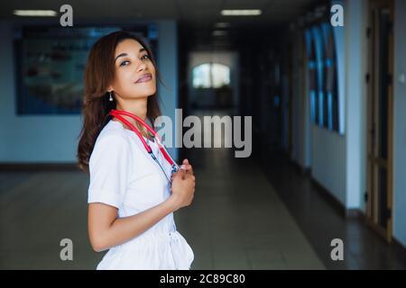 Estudiante de medicina africana sonriendo en la cámara de la universidad en un traje quirúrgico blanco.