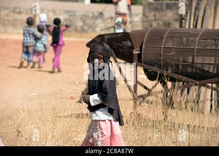 Una joven, indígena mandingo (mandinka) niña que camina de la escuela en su aldea, Gambia, África Occidental.