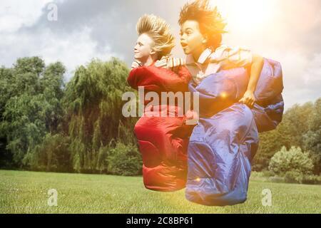 Dos chicos corriendo en sacos de dormir Foto de stock