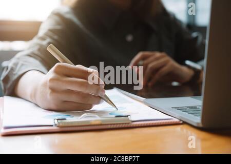 Businessman apunta la facturación con un informe gráfico y utiliza un ordenador portátil para analizar los datos