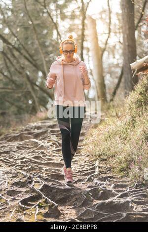 Una mujer deportiva activa que escucha la música mientras corre en otoño bosque de otoño. Entrenamiento de corredor femenino al aire libre. Imagen de estilo de vida saludable de los jóvenes