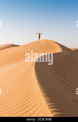 Hombre viajero parado en la cima de la duna, brazos hasta el cielo, mientras viaja postre de arena en Omán.