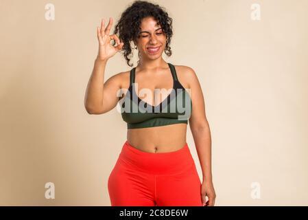 Mujer bastante grande llevando ropa deportiva posando en el estudio - hermosa chica aceptando la imperfección corporal, disparos de belleza en el estudio - conceptos sobre el cuerpo a