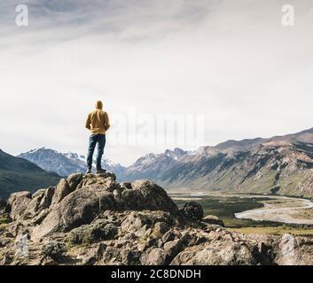 Hombre maduro con capucha mirando las montañas contra el cielo mientras está parado en roca, Patagonia, Argentina