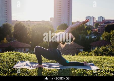 Mujer joven practicando yoga en posición de guerrero en el parque de la ciudad durante el día soleado