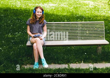 Chica sonriente escuchando música a través de los auriculares mientras se sienta en el banco en el parque