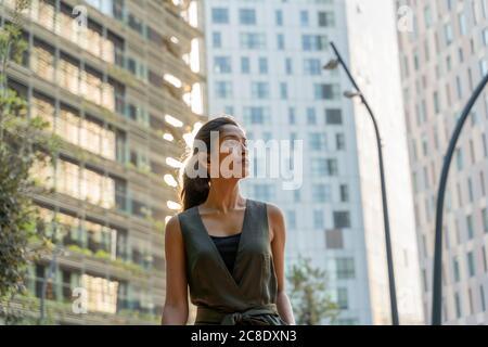 Una mujer pensativa mirando lejos mientras está de pie contra los edificios modernos