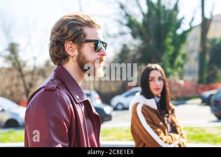 Primer plano de hombre con gafas de sol caminando con novia en la ciudad Foto de stock