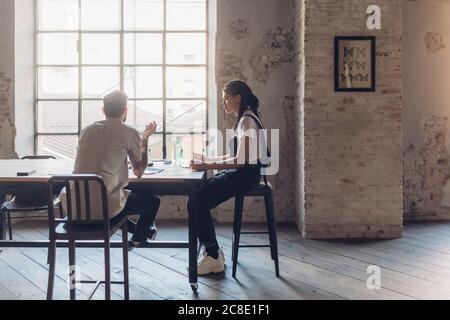 Dos personas creativas de negocios que tienen una reunión en la oficina del desván