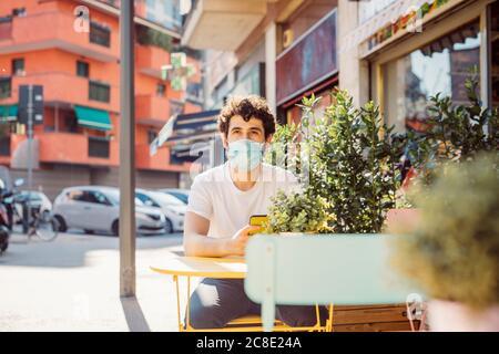Un joven pensativo que llevaba una máscara sentado en la cafetería de la acera ciudad