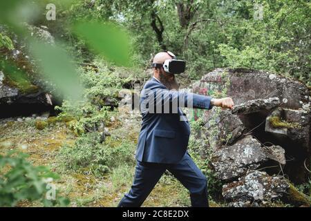 Hombre de negocios mirando a través de simulador de realidad virtual practicando artes marciales en bosque