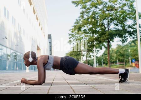 Mujer atleta escuchando música mientras practica tablones en el sendero ciudad