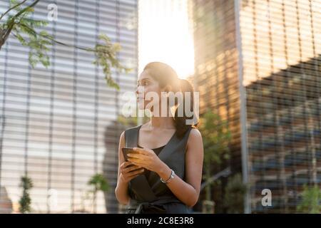 Una mujer de negocios pensativa sosteniendo un teléfono inteligente mientras estaba de pie contra edificios modernos