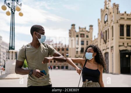 Hombre y mujer usando máscaras mientras se saludan unos con otros codos en la ciudad