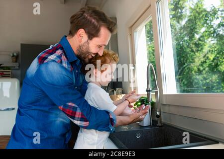 Hombre sonriente lavándose las manos con su hijo en el fregadero de la cocina inicio
