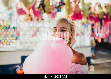 Primer plano de una joven sonriente con los ojos cerrados sosteniendo algodón dulces en el parque de atracciones Foto de stock