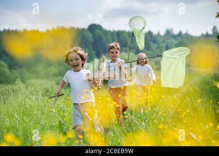 Amigos despreocupados con modelo de avión y redes de mariposa corriendo tierra verde en el bosque