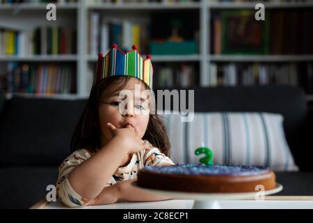 Retrato de la pequeña niña degustación pastel de cumpleaños