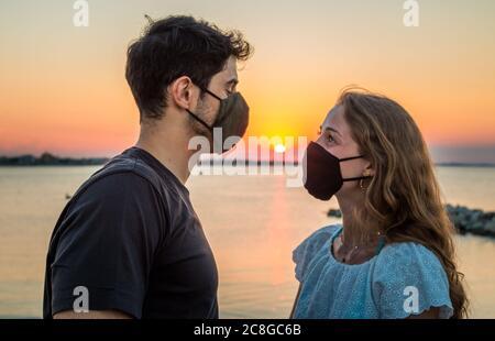 una pareja joven toma un selfie al atardecer usando máscara de cara - selfie durante el coronavirus - concepto sobre nuevo normal