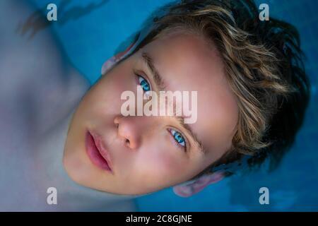 yong hombre con increíbles ojos azules en la piscina, disfrutando de sus vacaciones