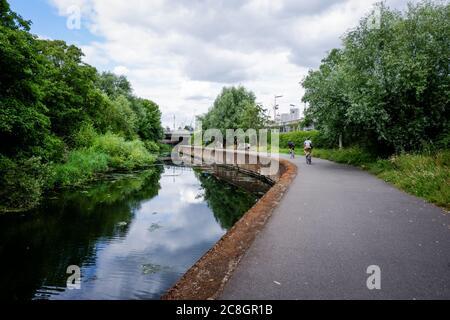 Ciclistas en el camino de sirga del río Lea que corre a través del Parque Olímpico Reina Elizabeth en Stratford, Newham Reino Unido 2020 Foto de stock
