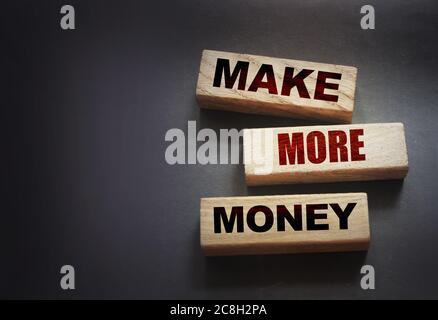Los bloques de madera con el texto hacen más dinero. Concepto de negocio o carrera