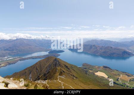 La vista desde la cumbre del pico Roys sobre el lago Wanaka y las montañas de los Alpes del Sur como las nubes se ruedan sobre ellos.
