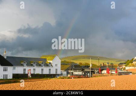 West Bay, Dorset, Reino Unido. 25 de julio de 2020. El tiempo en el Reino Unido. El sol sale después de fuertes lluvias claras con un arco iris sobre las casas frente al mar en el complejo turístico de West Bay en Dorset. Crédito de la imagen: Graham Hunt/Alamy Live News Foto de stock
