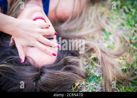 Retrato de cerca desde arriba de una hermosa y alegre chica caucásica riendo mucho y divirtiéndose mucho tumbarse en el césped en el aire libre AC