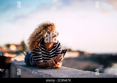 Hermosa mujer rubia de edad media rizado disfrutar y relajarse en actividades de ocio al aire libre mirando la puesta de sol con el teléfono moderno listo para llamar a amigos - p