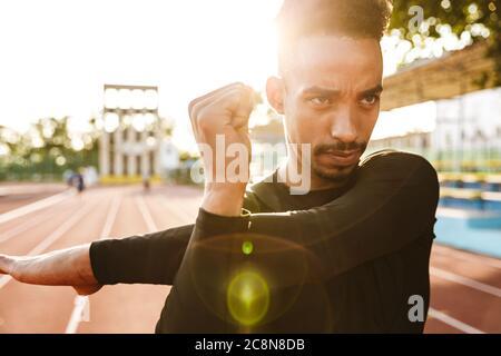 Imagen del hombre afroamericano centrada en ropa deportiva estirando sus brazos mientras hace ejercicio en la mañana en el estadio al aire libre