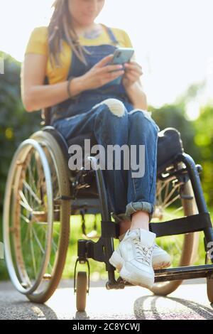 joven mujer atractiva en silla de ruedas texting con su teléfono móvil, discapacidad y concepto de empleo. de cerca foto recortada. fondo borroso Foto de stock