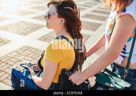 mujer con buen aspecto y estilo en gafas de sol sentada en la silla de ruedas, mujer ayudando a su hermana, ella se encarga de ella. de cerca vista lateral recortada foto. Foto de stock
