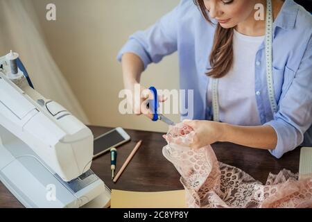 Caucásica concentrada costurera corte de encaje rosa, sentada en su lugar de trabajo con accesorios de sastre y costura mashine en el estudio, de cerca