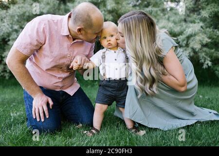 Los padres besan al bebé en el jardín