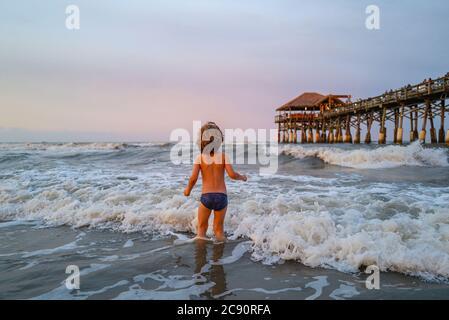 Niño pasarlo bien al aire libre. Vacaciones en el mar, niños divertidos, niños jugando en la playa del océano.