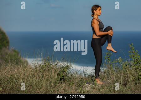 Mujer joven haciendo yoga al aire libre con una vista trasera increíble. Bali. Indonesia.