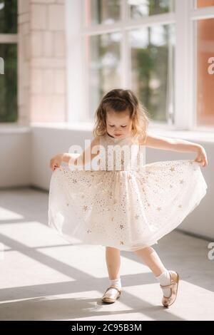 Cute niña de tres años de edad en vestido posando para el fotógrafo en el estudio. Beutiful niña danza