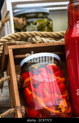 Jarras de vidrio con pimientos rojos en escabeche y botellas con salsa de tomate aisladas en una composición rústica. Jarras con variedad de verduras en escabeche pre