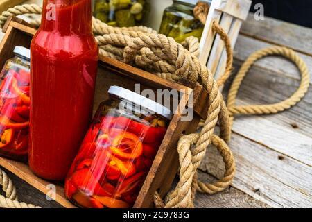 Caja de madera con botellas con salsa de tomate y tarros de vidrio con pimientos rojos encurtidos aislados en una composición rústica. Tarros con variedad de selección