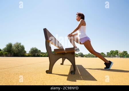 Mujer joven estirando sus músculos en un banco al aire libre antes de hacer deporte. Espacio para texto.