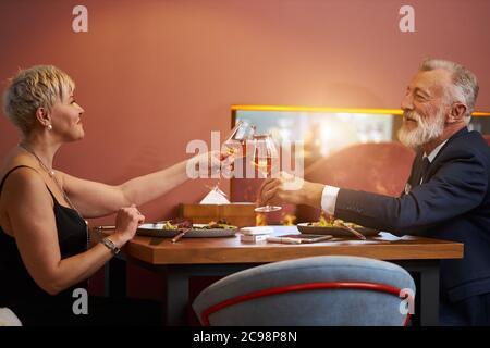 La pareja mayor elegante se sienta en el restaurante y las copas de los clink con champán, celebrar. Hombre de pelo gris barbudo en tuxedo y mujer caucásica en el dr negro