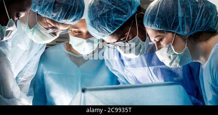 médicos talentosos y capacitados que examinan la enfermedad del paciente. de cerca fotografía recortada. médicos con máscaras mirando hacia abajo
