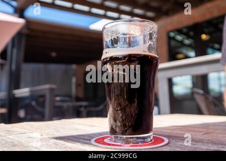 Una cerveza artesanal oscura, una cerveza de barril, en un cristal de pinta claro sentado en una montaña rusa roja y blanca.