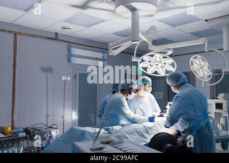 Cirujano masculino la celebración de instrumento en el abdomen del paciente. Los asistentes masculinos y femeninos que le ayude. Cirujano indio realizar cirugía laparoscópica en operación
