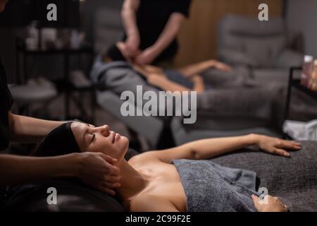 dos jóvenes mujeres caucásicas reciben un masaje anti envejecimiento en el cuello, las mujeres atractivas tienen descanso en el spa salón de bienestar, cuidado de la piel, el concepto de elevación de la cara
