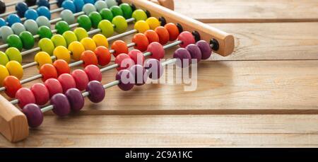 Abacus de la escuela con cuentas coloridas en el escritorio de madera, vista de cerca, espacio de copia. Los niños aprenden cuentan, los niños aprenden el concepto de la clase de matemáticas
